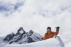 Stock Photo of Mountain Climber Reaching Over Snowy Peak