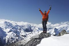 Mountain Climber With Arms Raised On Snowy Peak Stock Photos