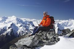 Stock Photo of Mountain Climber Using Laptop On Mountain Peak