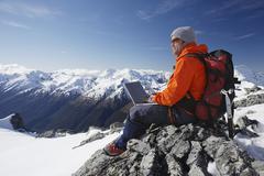 Mountain Climber Using Laptop On Mountain Peak - stock photo