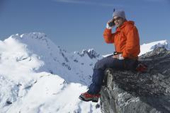 Mountain Climber Using Walkie Talkie Against Mountain Peak - stock photo