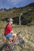 Cyclist Looking At Waterfall In Field Stock Photos