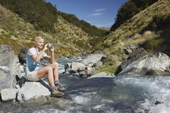 Woman Photographing Forest River - stock photo