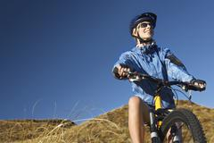 Woman Sitting On Bicycle In Field - stock photo