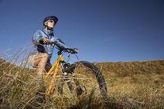 Woman Riding Bicycle In Field - stock photo