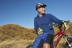 Man Leaning On Bicycle In Field Stock Photos