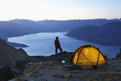 Man By Lake And Tent At Dusk - stock photo