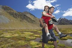 Man Giving Woman Piggyback Ride through Mountain Pond - stock photo