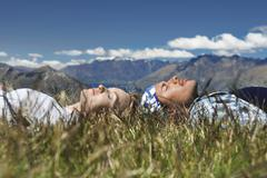 Couple Lying In Field Overlooking Hills - stock photo