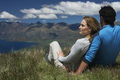 Stock Photo of Couple Looking Over Lake And Hills