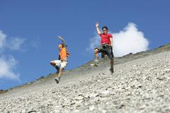 Two Men Jumping Down Scree Field - stock photo