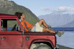 Man Lying On Jeep Hood By Mountain Lake - stock photo