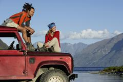 Couple Sitting On Jeep By Mountain Lake - stock photo