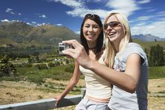 Two Women Photographing Themselves Against Countryside Fence - stock photo