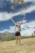 Female Hiker Throwing Grass Up In The air At Field Stock Photos