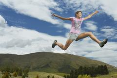 Stock Photo of Woman Leaping On Rural Landscape