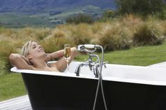 Stock Photo of Woman In Bathtub With Champagne On Countryside Porch