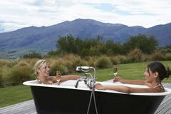 Women In Bathtub With Champagne Against Mountains Stock Photos