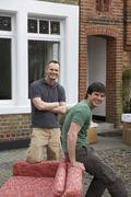 Stock Photo of Two Men With Sofa Outside House