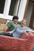 Stock Photo of Couple Sitting On Sofa Outdoors