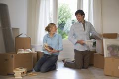 Stock Photo of Couple Unpacking Boxes At Home