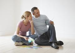 Couple Looking At Paint Swatches On Floor - stock photo