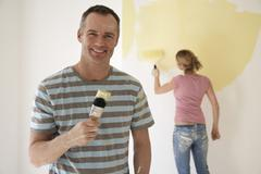 Smiling Man Holding Paintbrush While Woman Paints Wall With Roller Stock Photos