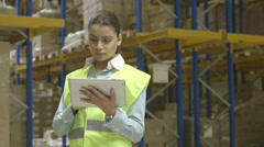Young woman using computer in logistics warehouse - stock footage