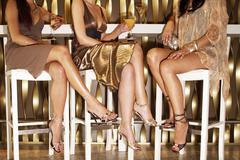 Stylishly Dressed Women Sitting At The Bar - stock photo