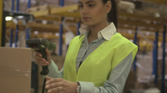 Young latin woman using a scanner to scan boxes in factory Stock Footage