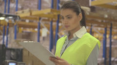 Young woman engineer standing and holding clipboard in factory warehouse - stock footage