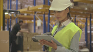 Stock Video Footage of Young latin woman using barcode reader and digital tablet in factory warehouse