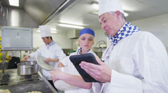 Professional chefs arranging their schedule in a restaurant or hotel kitchen - stock footage