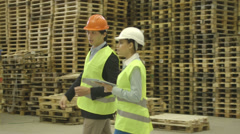 Two engineers using digital tablet and planning in factory Stock Footage