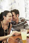 Man Whispering In Woman's Ears At Sidewalk Cafe Stock Photos