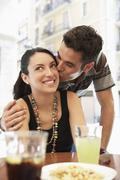 Man Kissing In Woman's Cheek At Sidewalk Cafe Stock Photos