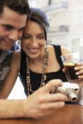 Couple Looking Photographs On Digital Camera At Sidewalk Cafe - stock photo