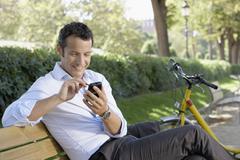 Businessman Using Palmtop Pilot On Park Bench - stock photo