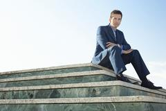 Portrait Of Smart Businessman Sitting On Marble Staircase - stock photo