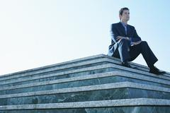 Businessman Looking Away While Sitting On Marble Staircase - stock photo