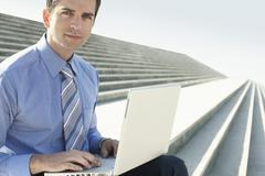 Confident Businessman With Laptop Sitting On Marble Staircase - stock photo