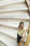 Stock Photo of Businesswoman Using Mobile Phone While Standing On Staircase