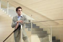 Thoughtful Businessman Looking Away While Leaning On Glass Railing - stock photo