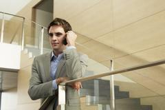 Businessman Using Cellphone While Leaning On Glass Railing Stock Photos
