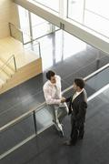 Businessmen Shaking Hands By Railing In Office - stock photo