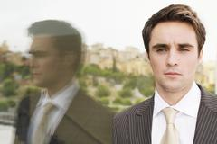 Stock Photo of Confident Businessman Standing By Glass Wall