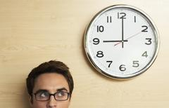 Businessman Looking At Clock On Wooden Wall In Office - stock photo
