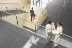 Business Colleagues Discussing By Railing In Office Stock Photos