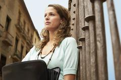 Woman Holding Briefcase Leaning Against Railing Stock Photos