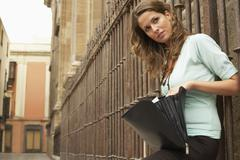 Woman Holding Open Briefcase Against Railing - stock photo